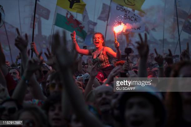 TOPSHOT Revellers watch as British singer Liam Gallagher performs on the Pyramid Stage at the Glastonbury Festival of Music and Performing Arts on...