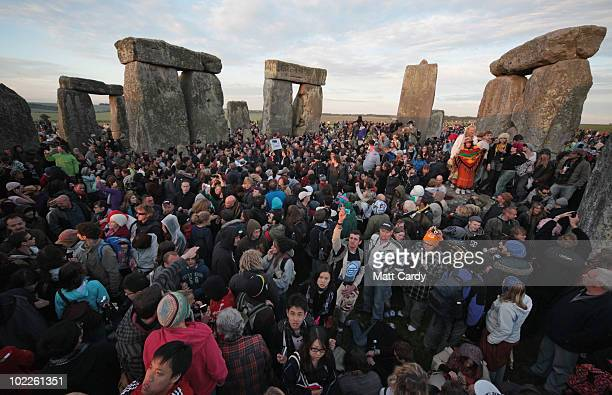 Revellers watch as the midsummer sun rises just after dawn over the megalithic monument of Stonehenge on June 21 2010 on Salisbury Plain England...