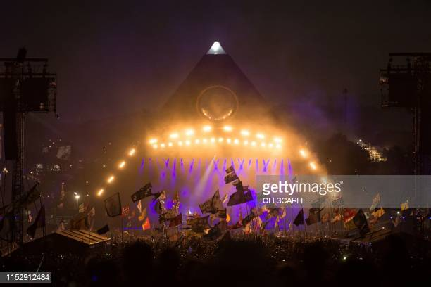 Revellers watch as US band The Killers perform on the Pyramid Stage at the Glastonbury Festival of Music and Performing Arts on Worthy Farm near the...