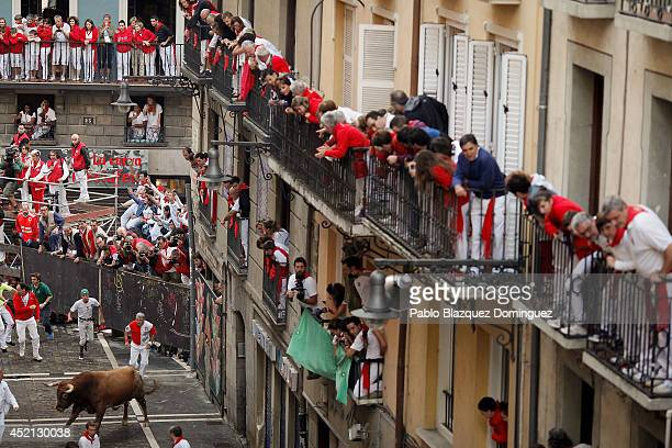 Revellers watch from balconies as the last Miura's fighting bull turns towards runners at Curva Estafeta during the ninth day of the San Fermin...