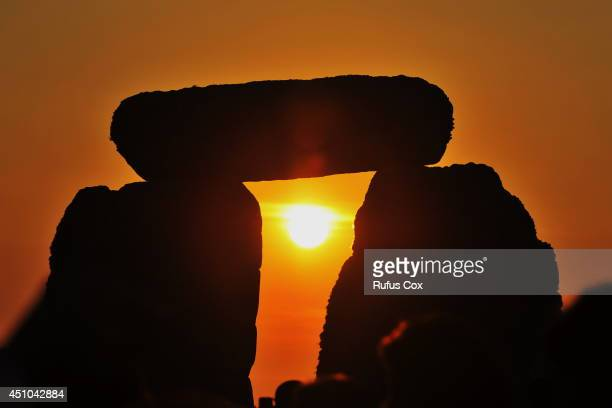Revellers watch sunrise over Stonehenge during celebrations to mark the summer solstice at the prehistoric monument on June 21 2014 in Wiltshire...