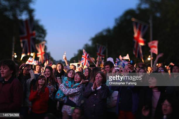 Revellers watch the concert on giant screens on the The Mall as thousands gather for The Diamond Jubilee Concert on June 4, 2012 in London, England....