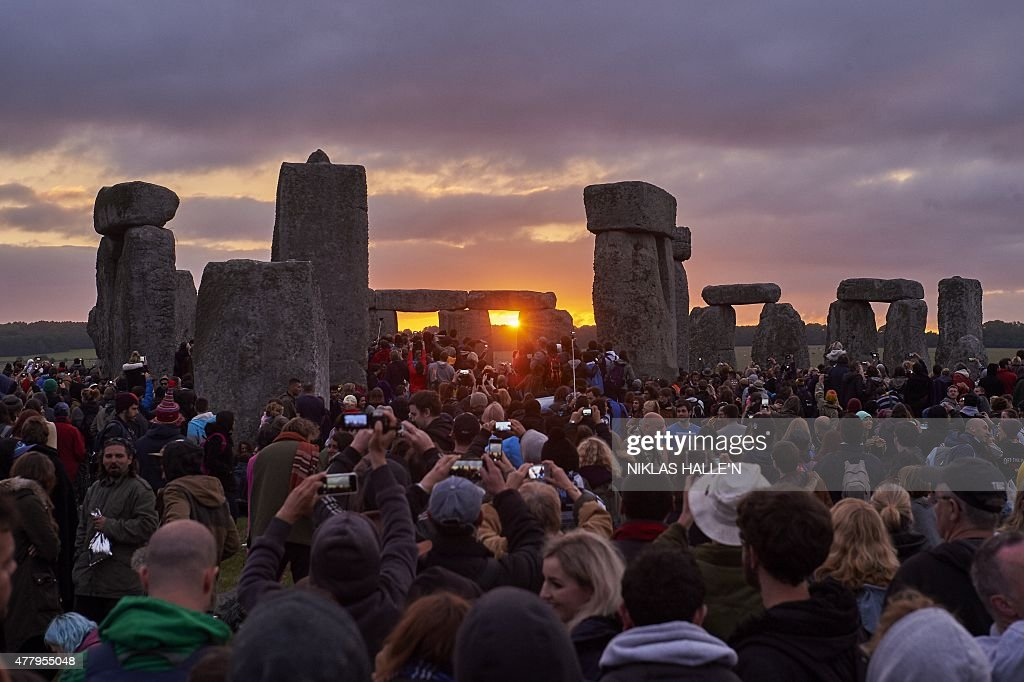 Revellers watch the sunrise as they celebrate the pagan festival of Summer Solstice at Stonehenge in Wiltshire, southern England on June 21, 2015. The festival, which dates back thousands of years, celebrates the longest day of the year when the sun is at its maximum elevation. Modern druids and people gather at the landmark Stonehenge every year to see the sun rise on the first morning of summer. AFP PHOTO/NIKLAS HALLE'N