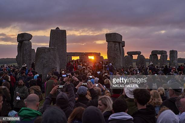 Revellers watch the sunrise as they celebrate the pagan festival of Summer Solstice at Stonehenge in Wiltshire southern England on June 21 2015 The...
