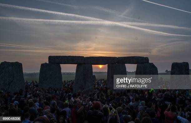 Revellers watch the sunrise as they celebrate the pagan festival of Summer Solstice at Stonehenge in Wiltshire southern England on June 21 2017 The...
