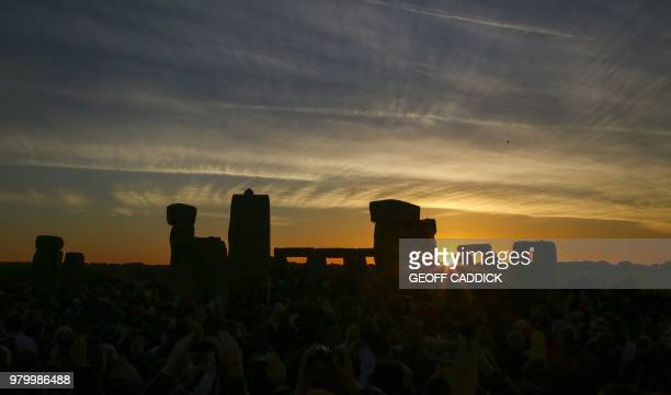 TOPSHOT Revellers watch the sunrise as they celebrate the pagan festival of Summer Solstice at Stonehenge in Wiltshire southern England on June 21...
