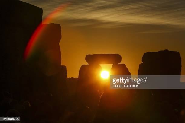 Revellers watch the sunrise as they celebrate the pagan festival of Summer Solstice at Stonehenge in Wiltshire southern England on June 21 2018 The...