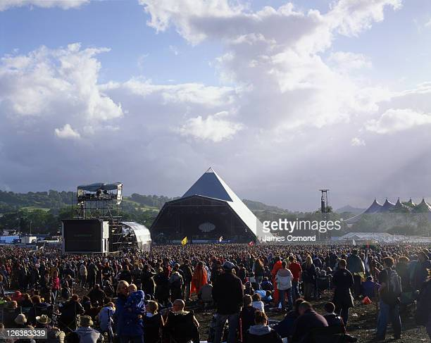 revellers watching a performance on the pyramid stage at the glastonbury festival. - glastonbury stock pictures, royalty-free photos & images