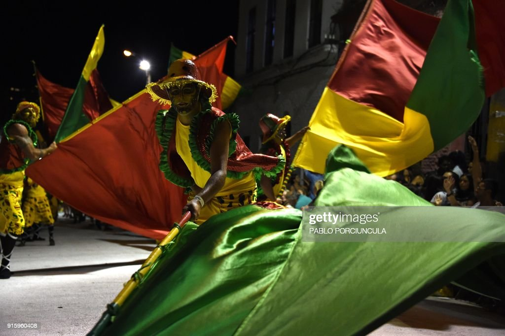 Revellers wave giant flags as they perform during carnival on a street in Montevideo on February 8, 2018. The 'Llamadas' is Uruguay's biggest carnival parade, in which 'comparsas' -- groups of dancers and drummers playing and dancing to the traditional 'candombe' music -- compete during two nights of parades. / AFP PHOTO / Pablo PORCIUNCULA