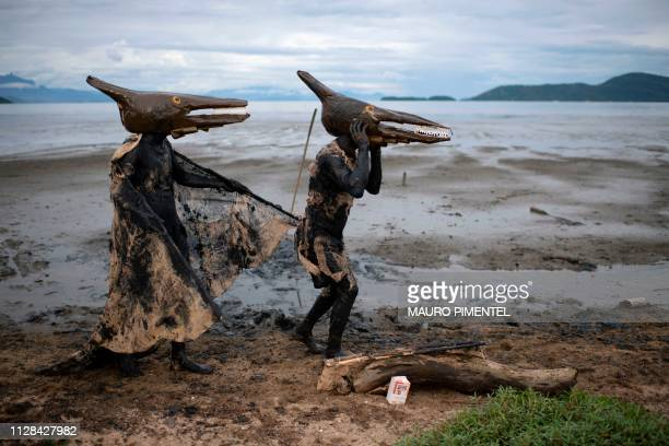 Revellers wearing Pterodactyl costumes take part in the Bloco da Lama a mud carnival party in Paraty Rio de Janeiro state Brazil on March 02 2019...