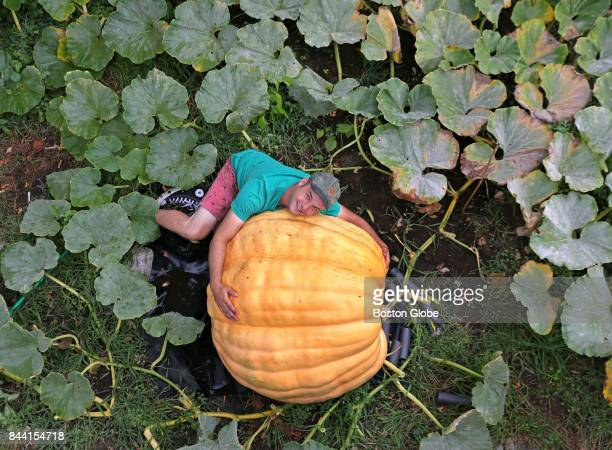 Revere resident Christian Ilsley poses with the giant pumpkin he is growing in his backyard in Revere MA on Sep 6 2017 He plans to hollow it out and...