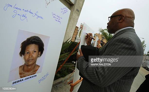 Reverend Dr Kelvin Calloway who is from a church close to the crime scenes leaves a message on photographs set up as a memorial for 10 of the victims...