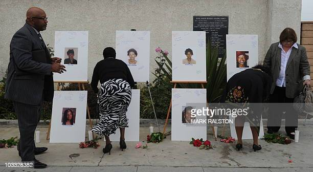 Reverend Dr Kelvin Calloway who is from a church close to the crime scenes and others leave messages on photographs set up as a memorial for 10 of...