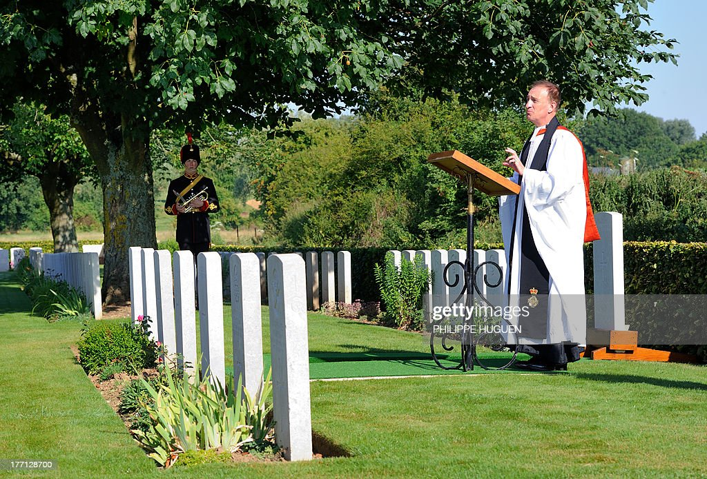 Reverend Dr Simon Bloxam-Rose speaks on August 21, 2013 during the burial of an unknown soldier at the Fifteen Ravine British Cemetery in Villers-Plouich, northern France. 'Fifteen Ravine' was the name given by the Army to the shallow ravine, once bordered by fifteen trees, which ran at right angles to the railway about 800 metres south of the village of Villers-Plouich. The cemetery, sometimes called Farm Ravine Cemetery, was begun by the 17th Welsh Regiment in April 1917, a few days after the capture of the ravine by the 12th South Wales Borderers. It continued in use during the Battle of Cambrai (November 1917) and until March 1918, when the ravine formed the boundary between the Third and Fifth Armies. On 22 March, the second day of the great German offensive, the ground passed into their hands after severe fighting, and it was not regained until the end of the following September. In March 1918, the cemetery contained 107 graves (now Plot I), but it was greatly enlarged after the Armistice when graves were brought in from the battlefields south-west of Cambrai and other cemeteries.
