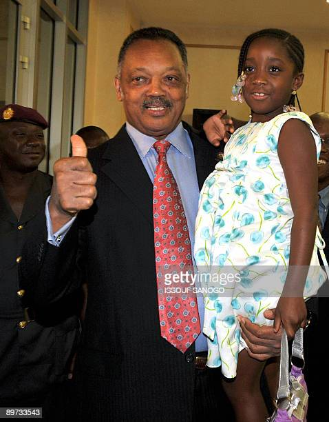 US Reverend Jesse Jackson gives a thumbs up as he poses with Obre one of the grand children of Ivory Coast President Laurent Gbagbo at the...