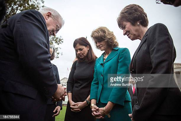 Reverend Jim Wallis prays with Sen. Kelly Ayotte , Sen. Lisa Murkowski and Sen. Susan Collins in front of the Capitol Building on the morning of...