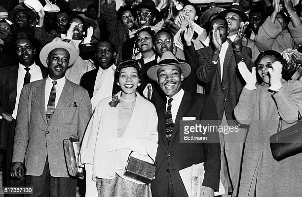 Reverend Martin Luther King Jr and his wife Coretta Scott King smile broadly as they stand in front of a group of cheering followers after King's...