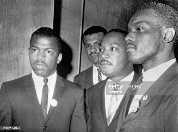 Reverend Martin Luther King Jr is escorted into a mass meeting at Fish University in Nashville His colleagues are left to right John Lewis national...