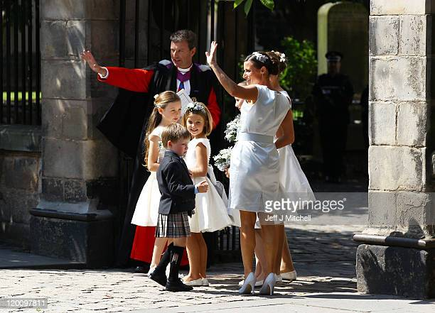 Reverend Neil Gardner and The flower girls and bridesmaids wave as they arrive for the Royal wedding of Zara Phillips and Mike Tindall at Canongate...