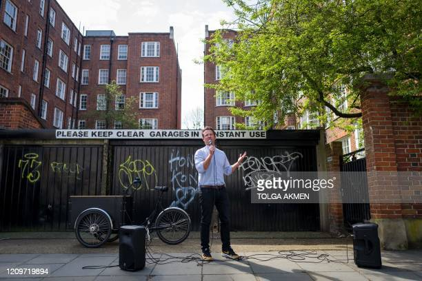 Reverend Patrick Allerton delivers his prayers and songs for Easter in the streets of Notting Hill in west London on April 12 during the nationwide...