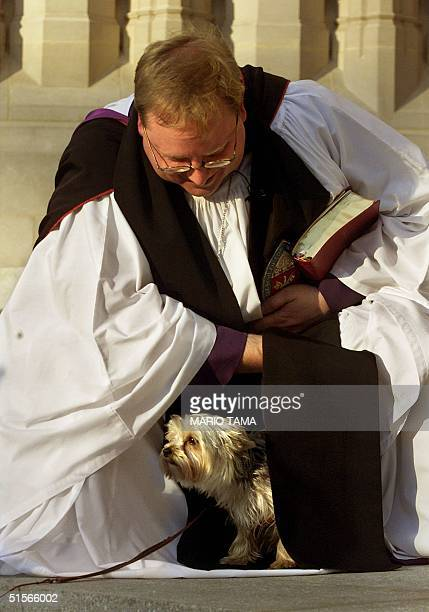 Reverend Peter Grandell attempts to corral Peekaboo a yorkshire terrier during a blessing of animals at Washington National Cathedral 04 October 2000...