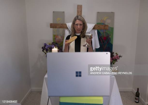 Reverend Sarah Scherschligt, Pastor at the Peace Lutheran church, holds communion during an online streaming service from the basement of her home in...