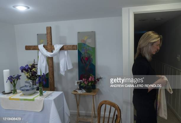Reverend Sarah Scherschligt Pastor at the Peace Lutheran church prays as she prepares to hold an online streaming service from the basement of her...