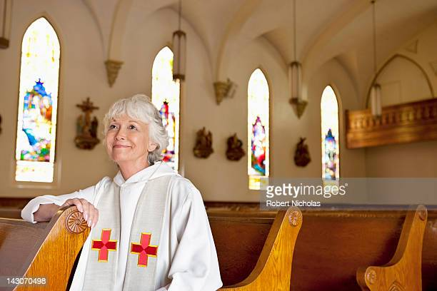 Reverend sitting in church pews