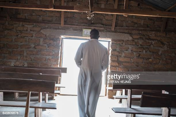A reverend walks in Saint Moses Catholic Church in the village of Bakin Kogi in Kaduna state northwest Nigeria that was recently attacked by...