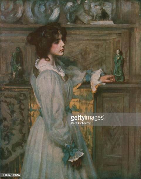 Reverie' A woman stands lost in thought in front of a mantelpiece with the glow of a fire behind her Painting in the Walker Art Gallery Liverpool...