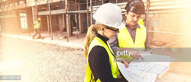Reviewing blueprints on a construction site