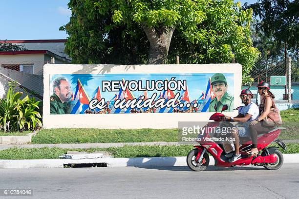 Revolution is Unity billboard depicting Fidel Castro and Raul Castro images Cuba people everyday transportation