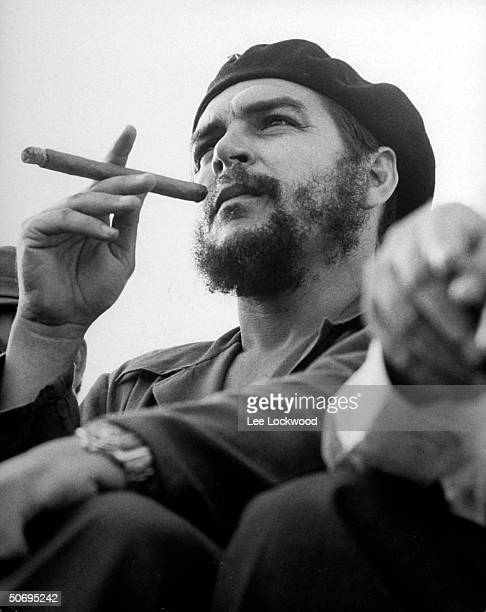 Revolutionary Che Guevara sitting on viewing stand smoking big cigar at an anniversary celebration of the Cuban revolution