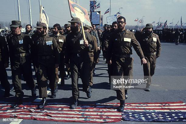 Revolutionary Guards or 'Pasdaran' in green uniforms march over a US flag spread on the tarmac in Azadi square Tehran whilst carrying banners with...