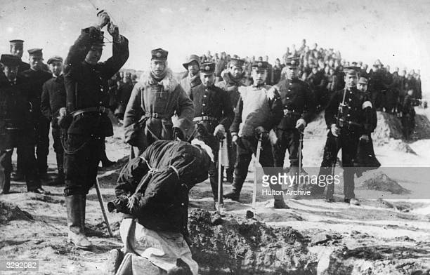 A revolutionist kneeling at the side of a grave his arms tied awaiting the death blow which will send him to his grave in the Chinese Revolution 1912