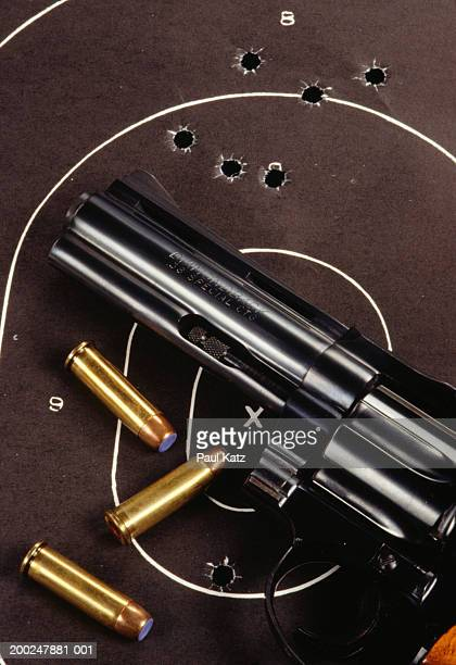Revolver and bullets lying on paper target, (Close-up)