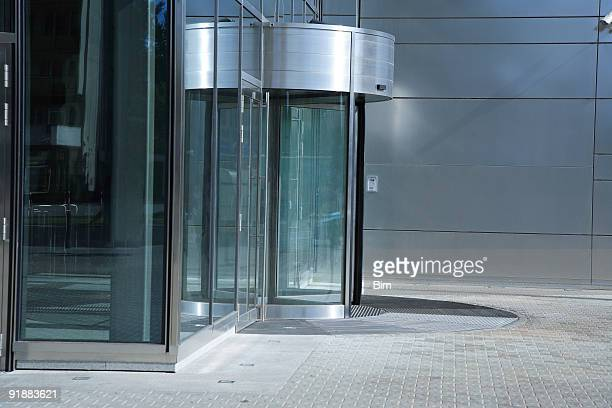 revolving door, entrance to modern office building - revolve stock photos and pictures
