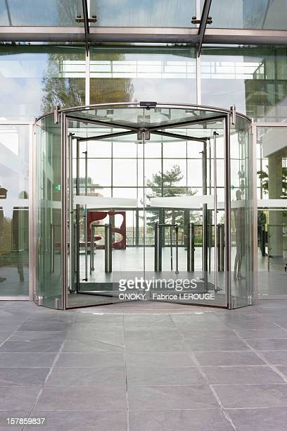 revolving door of an office building - revolve stock photos and pictures
