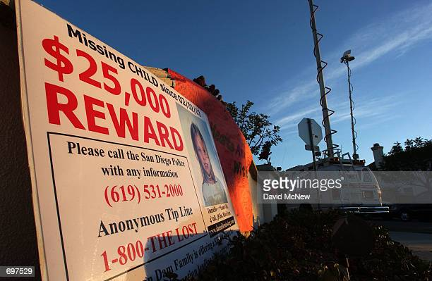 A reward poster near television news trucks advertises the newly increased $25000 reward from the van Dam familys personal funds in the hopes of...
