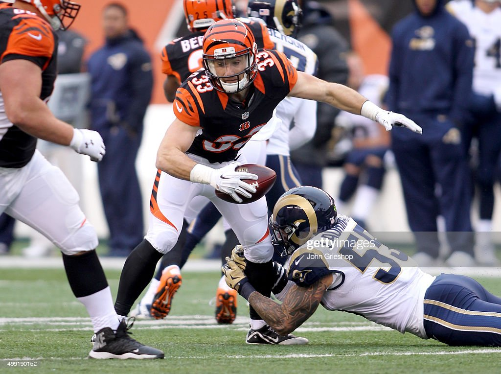 Rex Burkhead #33 of the Cincinnati Bengals attempts to evade a tackle attempt by James Laurinaitis #55 of the St. Louis Rams at Paul Brown Stadium on November 29, 2015 in Cincinnati, Ohio.