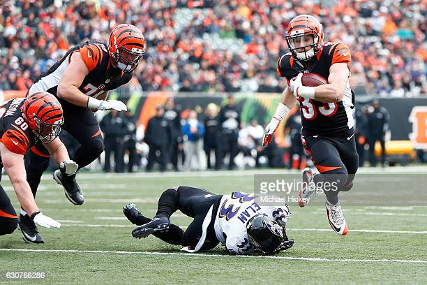 Rex Burkhead of the Cincinnati Bengals breaks a tackle by Matt Elam of the Baltimore Ravens to score a touchdown during the first quarter at Paul...