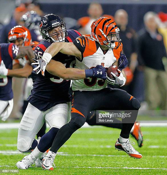 Rex Burkhead of the Cincinnati Bengals is wrapped up by Brian Cushing of the Houston Texans at NRG Stadium on December 24 2016 in Houston Texas...