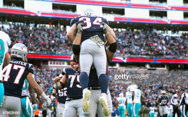 Rex Burkhead of the New England Patriots is picked up by a teammate after scoring a touchdown during the second quarter of a game against the Miami...