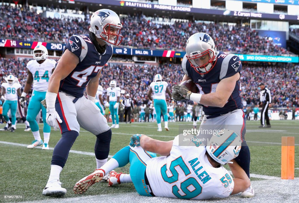 Rex Burkhead #34 of the New England Patriots reacts with Jacob Hollister #47 after scoring a touchdown while being defended by Chase Allen #59 of the Miami Dolphins during the second quarter of a game at Gillette Stadium on November 26, 2017 in Foxboro, Massachusetts.