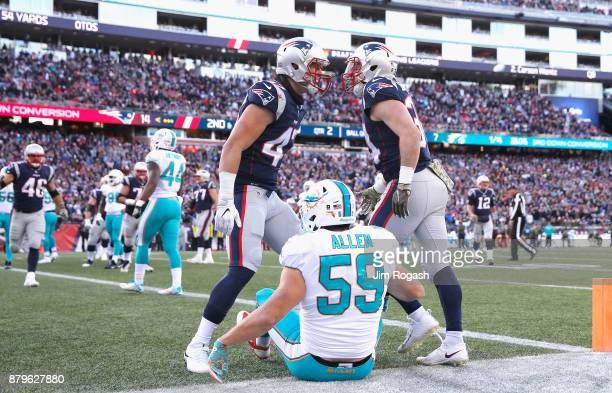 Rex Burkhead of the New England Patriots reacts with Jacob Hollister after scoring a touchdown while being defended by Chase Allen of the Miami...