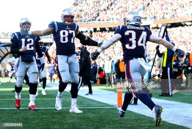 Rex Burkhead of the New England Patriots reacts with Rob Gronkowski and Tom Brady after scoring a touchdown during the second quarter in the AFC...