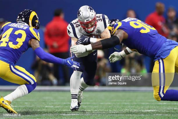 Rex Burkhead of the New England Patriots runs the ball against Michael Brockers of the Los Angeles Rams in the first half during Super Bowl LIII at...