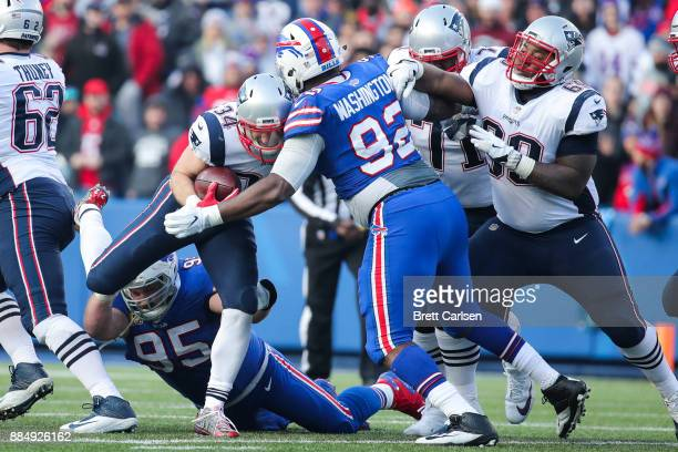 Rex Burkhead of the New England Patriots runs the ball as Adolphus Washington of the Buffalo Bills attempts to tackle him during the third quarter on...