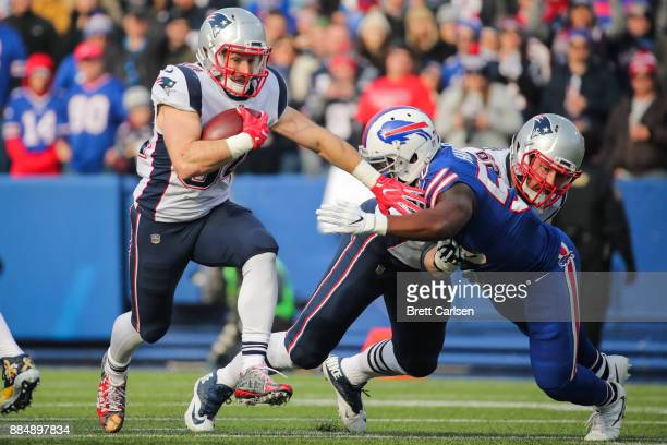 Rex Burkhead of the New England Patriots runs the ball as Jerry Hughes of the Buffalo Bills attempts to tackle him during the first quarter on...