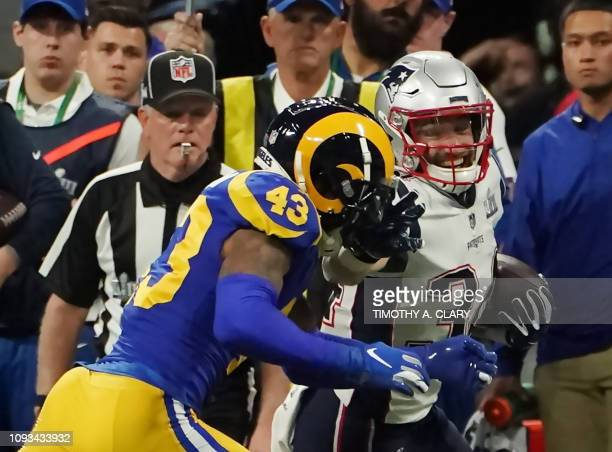 Rex Burkhead of the New England Patriots runs with the ball past strong safety for the Los Angeles Rams John Johnson III during Super Bowl LIII...